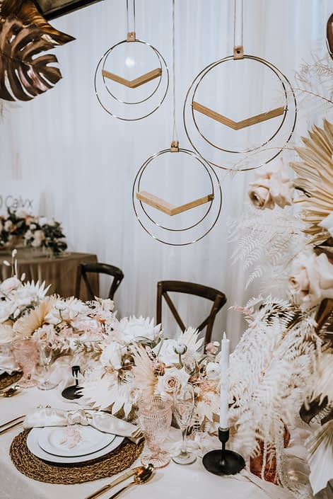 Display at the With This Ring Bridal Gala 2020 featuring ivory, blush pink, wood, and metallic gold accents with both fresh and dried botanicals.