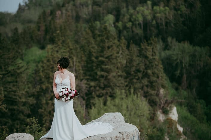 Bride, Sandra, standing on a cliff and holding her pink and burgundy bouquet designed with helleborus, peonies, ranunculus, black bacarra roses, blackberry scoop scabiosa, tulips, astrantia and eucalyptus.