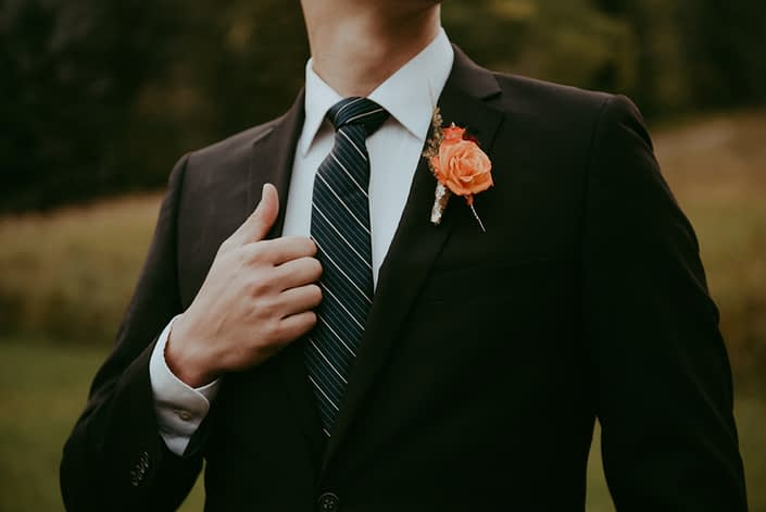 Bold orange boutonniere designed with a rose