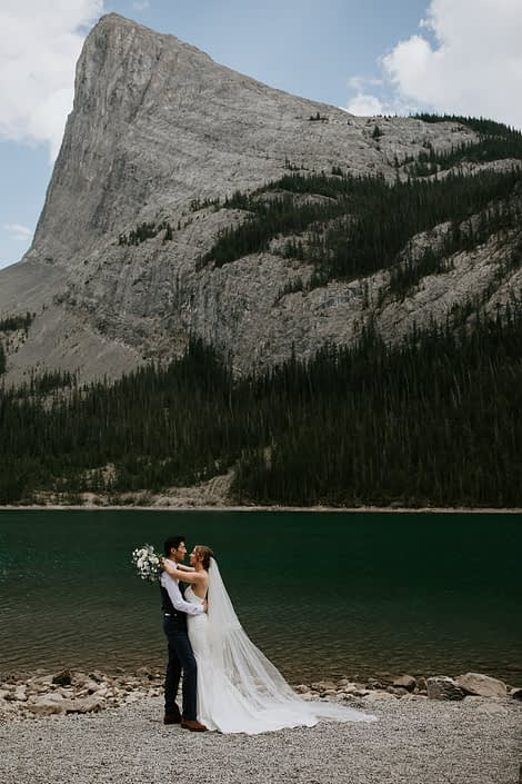 Bride and groom kissing near Canmore Rocky Mountains with white and blue bridal bouquet