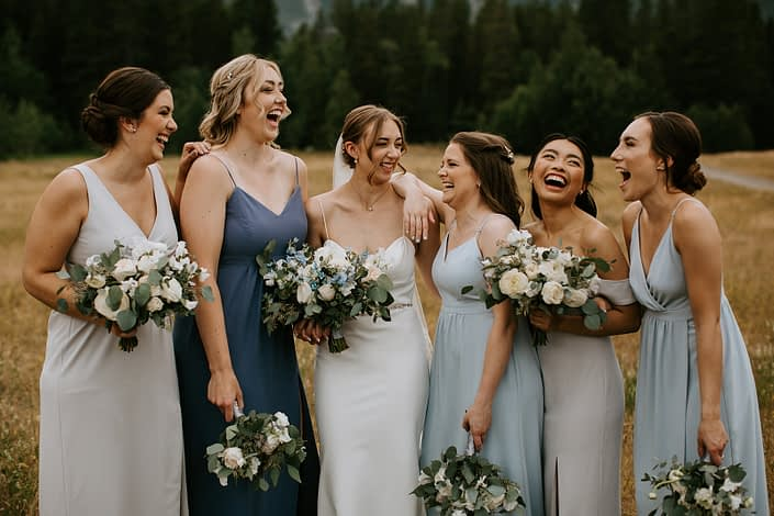 White and Blue Canmore Wedding - Bride with bridesmaids; white and blue dresses; white and blue bouquets featuring roses, ranunculus, sweet peas, forget me nots, eryngium, delphinium and eucalyptus