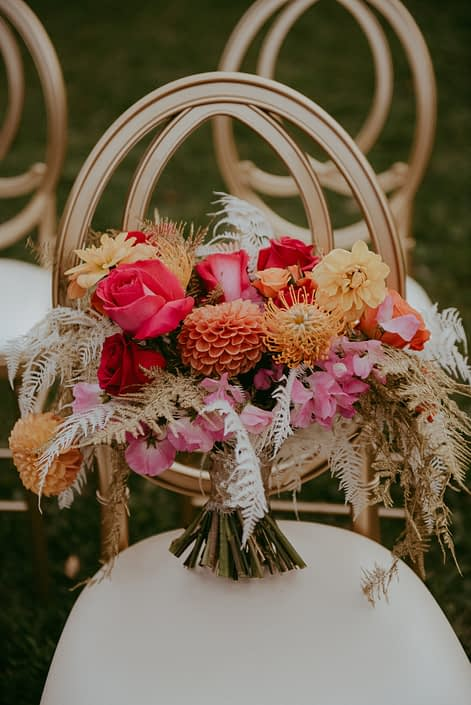 Fuchsia, orange and gold bouquet designed with zinnias, roses, dahlias, anemones, sweet peas, bleached bracken fern, and gold plumosa