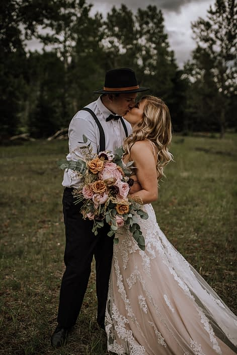 bride and groom in black hat kissing holding a bridal bouquet in an organic shae with toffee roses, pik oahra garden roses and cinerea eucalytpus