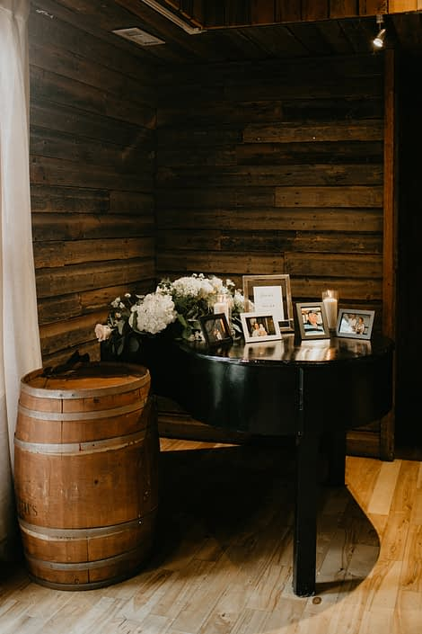 Grand piano covered with photos, candles and white hydrangea flower arrangement