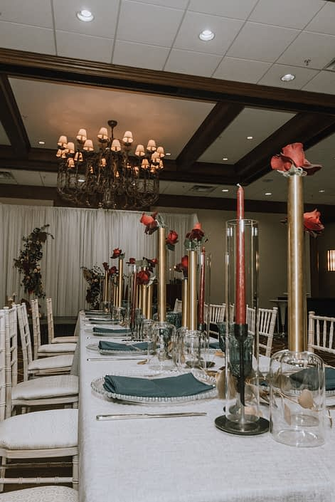 Cambridge Bridal Show 2020 - long table with white chairs, blue napkins and tall gold cylinder vases and red roses.