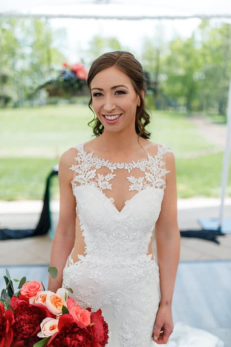 bride in white lace wedding dress holding a bouquet of burgundy peony, peach garden roses and coral amsterdam roses