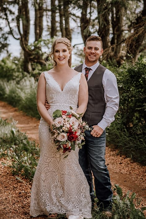 Groom wearing a grey vest and jeans standing with bride wearing a white lace gown and holding a rustic red and blush bridal bouquet featuring red charm peonies, quicksand roses, blush spray roses, burgundy astrantia, light pink astilbe and eucalyptus greenery.
