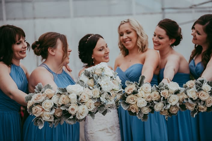 Bride and bridesmaids in sky blue holding bouquets of pale peach and ivory roses with grey dusty miller