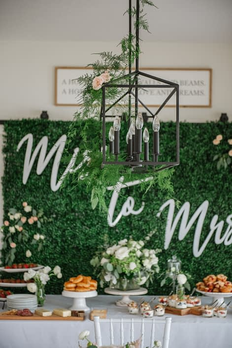 Bridal shower decor with boxwood backdroo, plumosa decorated chandelier and fresh flowers arrangements and dessert table