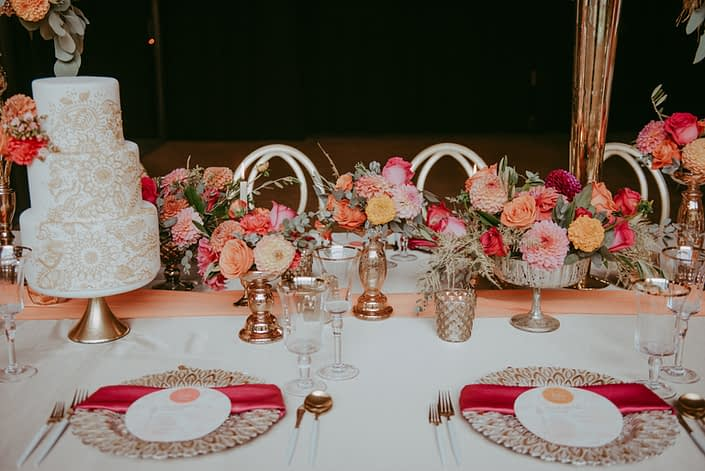 Bold and colourful fuchsia and orange compote arrangements designed in gold vases.