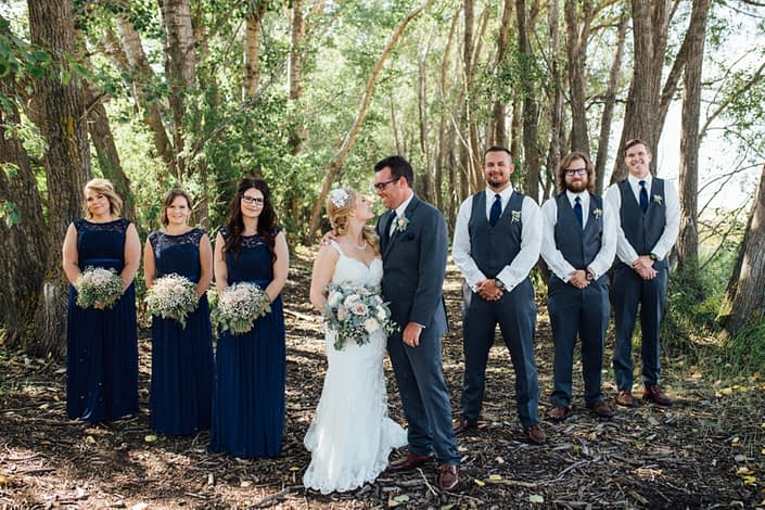 Bridal party for Kelsie and Kyle's Blush and Blue Vintage Barn Wedding - bride holding bouquet designed with blue delphiniums, quicksand roses, white o'hara garden roses, babies breath, succulents and eucalyptus; groom and groomsmen wearing matching boutonnieres, bridesmaids holding bouquets designed with babies breath, quicksand roses and eucalyptus.
