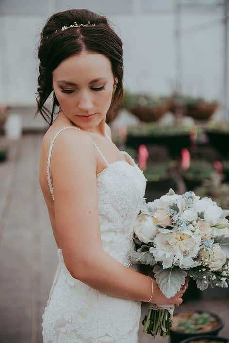 bride holding a bouquet of white peony, ivory rose and dusty miller