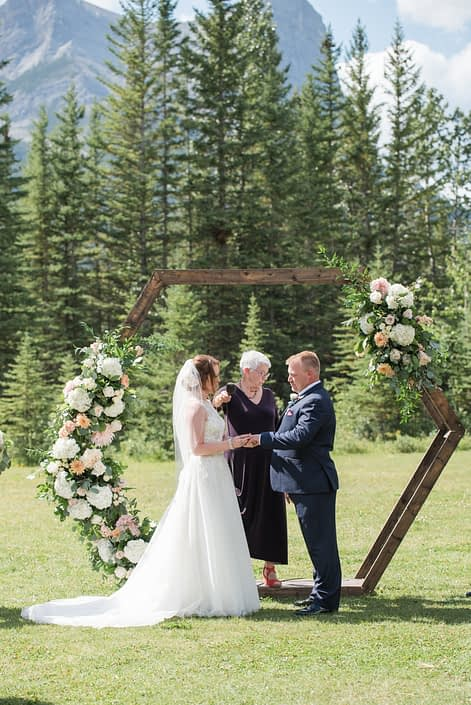 Amy and Kerry standing in front of the wooden hexagon archway at the ceremony. The archway is decorated with fresh floral arrangements designed with white hydrangeas, peach chrysanthemums, white o'hara garden roses, quicksand roses, astilbe, salal and eucalyptus.