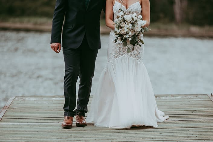 Bride and groom on a dock with white bridal bouquet featuring roses, ranunculus, sweet peas, astilbe and eucalyptus