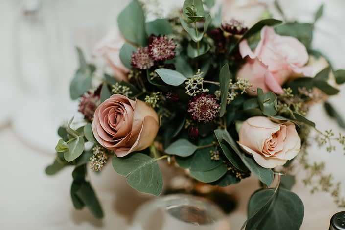 Compote centrepiece designed with burgundy astrantia, white ranunculus, amnesia roses, faith roses, quicksand roses and eucalyptus greenery in a gold mercury glass compote vase.