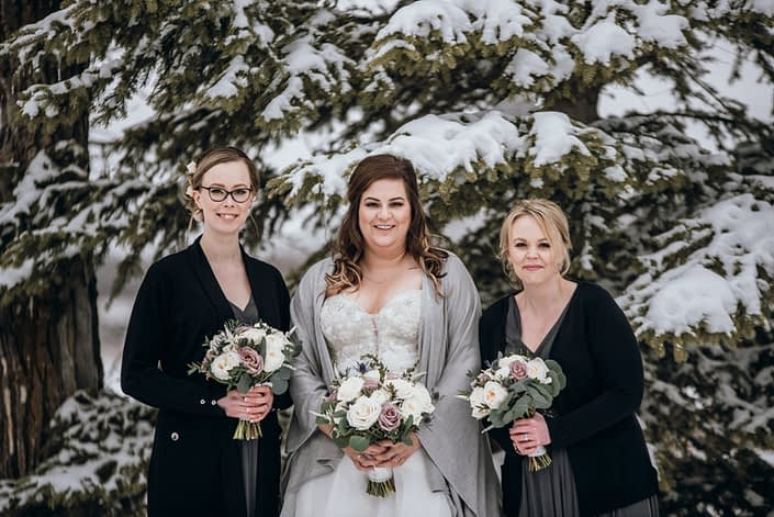Bride and bridesmaids carrying mauve and ivory bouquets designed with astilbe, eryngium, white o'hara garden roses, ranunculus, amnesia roses, playa blanca roses, and eucalyptus