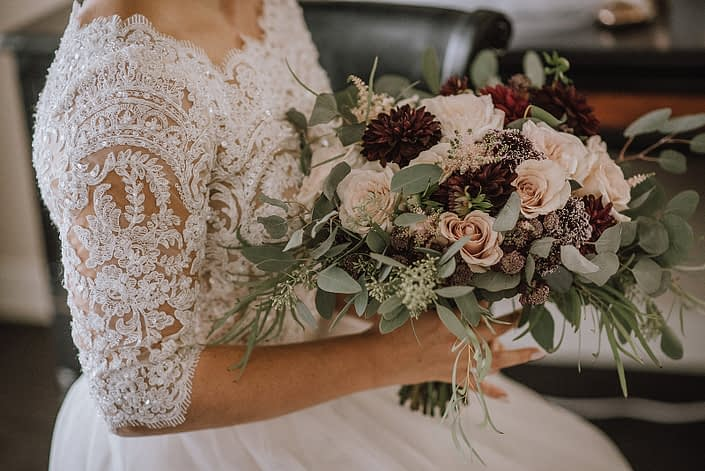 bride with lace top wedding dress holding a bouquet designed with ivory garden roses, burgundy dahlia, plum astrantia, burgundy scabiosa and pale pink astilbe with silver dollar and seeded eucalyptus