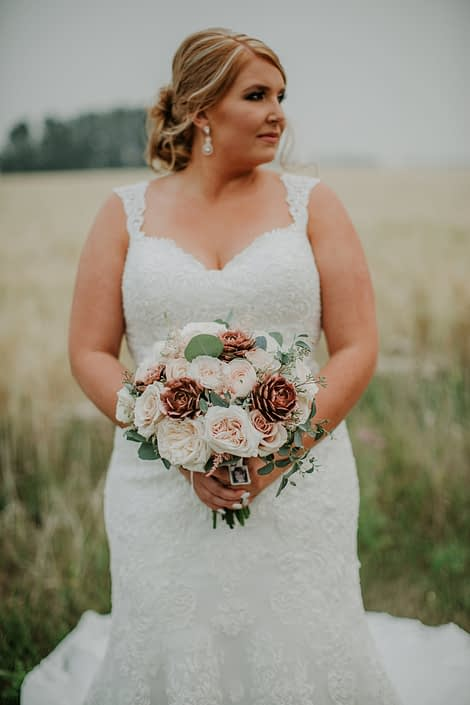 Bride in a late summer wheat field in alberta holding a bridal bouquet designed with rose gold succulents ad white ohara garden roses and blush quicksand roses