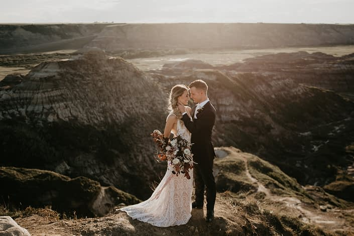 bride in a lace dress holding an organic bridal bouquet and groom overlooking the badlands in drumheller at sunset