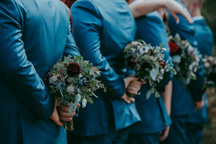Royal blue suited groomsmen holding burgundy and blue bouquets behind their backs