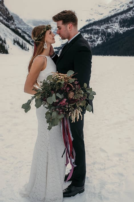 bride and groom at lake louise alberta with eucalyptus greenery bouquet and burgundy orchids