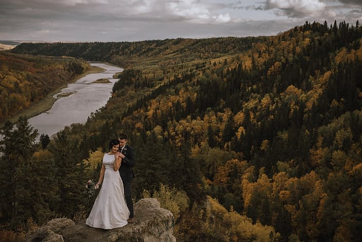 bride and groom wedding photos at Canyon Ski Resort overlooking the red deer river with burgundy and navy bridal bouquet
