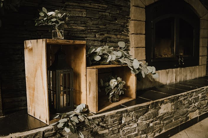 main room fireplace at Canyon Ski Resort decorated with wooden crates, lanterns and fresh eucalyptus greenery