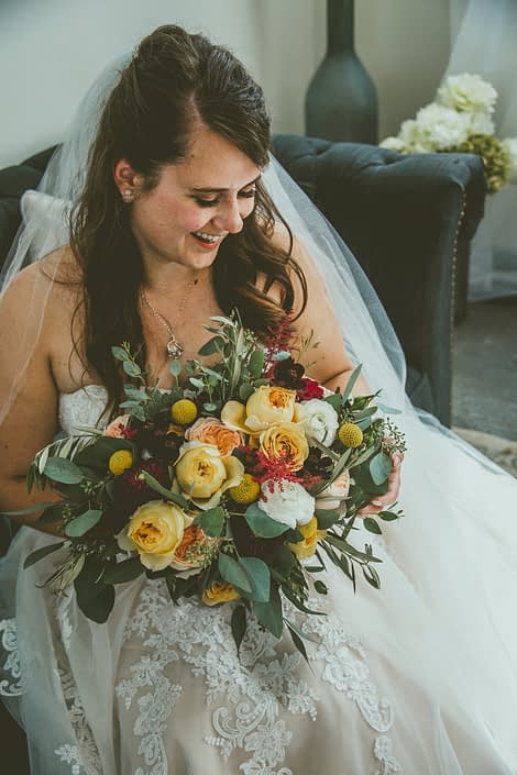 Bride, Bianca, with mustard yellow bridal bouquet featuring golden mustard roses, caramel antike garden roses, juliet garden roses, white ranunculus, plum dahlias, billy balls, red astilbe, olive branches and eucalyptus.