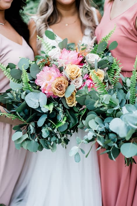Bridal bouquet made of coral charm peonies, golden mustard roses, quicksand roses, cappuccino roses, astilbe, astrantia, boston fern, monstera leaf and a mixed variety of eucalyptus amongst bridesmaids bouquets made of eucalyptus and boston fern.