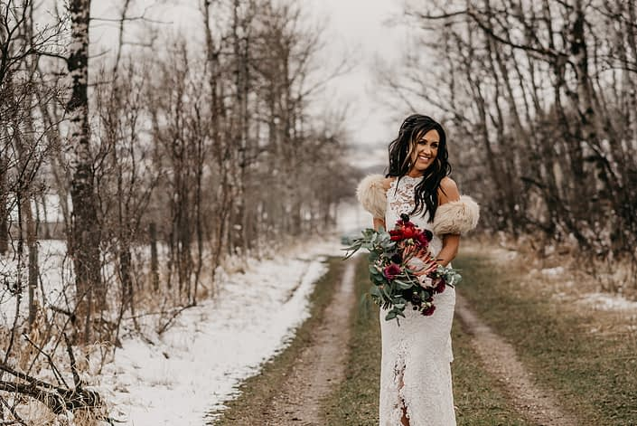 Rustic Boho Chic Wedding - Bride wearing ivory lace dress and fur shawl covering her shoulders while holding bridal bouquet made of king protea, red peonies, pink roses, plum scabiosa, panda anenome, and eucalyptus greenery.