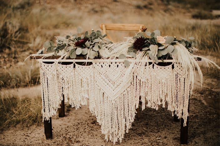 Macrame and flowers cover sweetheart table