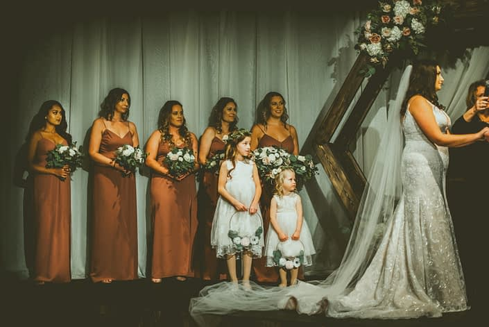 Bridesmaids wearing mauve dresses and holding blush and mauve bouquets standing with flower girls wearing flower crowns and carrying floral hoops. Hexagon archway decorated with an arrangement made of blush, mauve and white flowers and greenery.