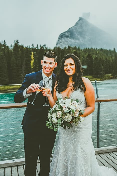Meagan and Dwayne holding champagne and her bridal bouquet in the Rocky Mountains.