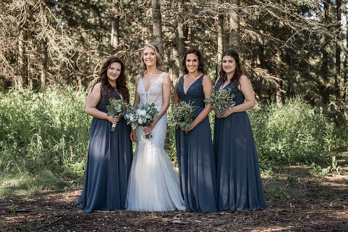 Bride with bridesmaids wearing blue floor length gowns and carrying greenery bouquets and blue and white bridal bouquet
