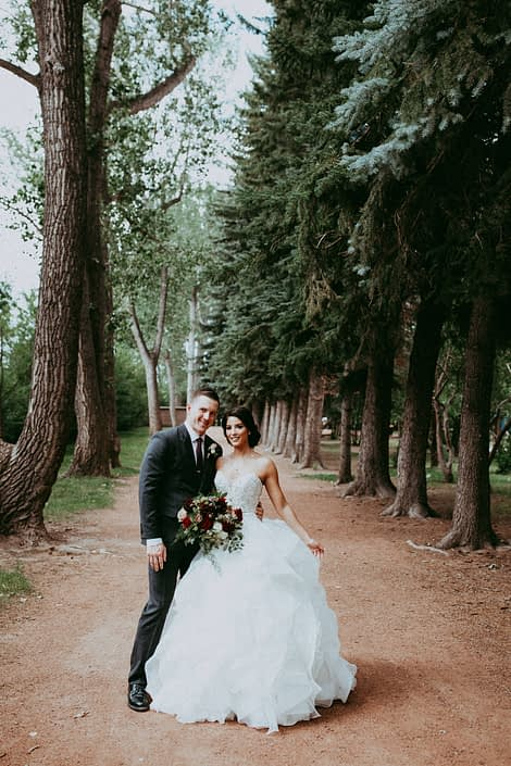 Burgundy and Dark Grey Wedding Bride and Groom with bouquet made of burgundy dahlias, amnesia roses, hearts garden roses and black pearl lisianthus with eucalyptus and plumosa greenery