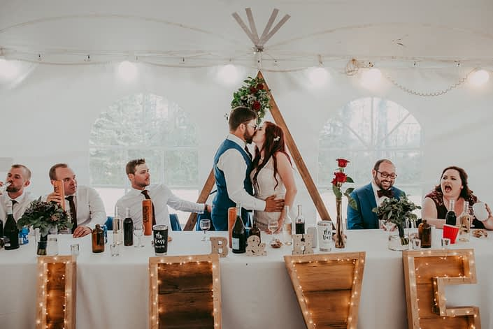 Bride and groom kissing at the head table for burgundy and royal blue wedding