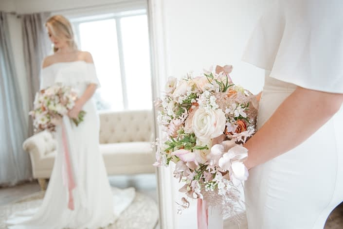 Bride in mirror with close up of pink, white and rose gold bridal bouquet designed with ranunculus, alyssum, hellebores, plumosa, eucalyptus