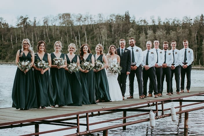 Natural White and Green wedding bridal party; bridesmaids wearing green gowns and holding white and green bouquets; groom and groomsmen wearing boutonnieres