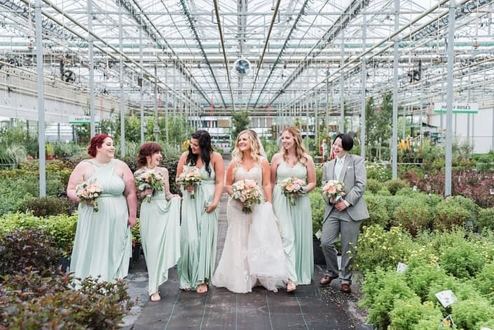 Megan and her bridesmaids in a greenhouse. The bridesmaids are wearing mint floor length gowns and they are all carrying blush pink bouquets made of roses, lisianthus, dusty miller and eucalyptus.