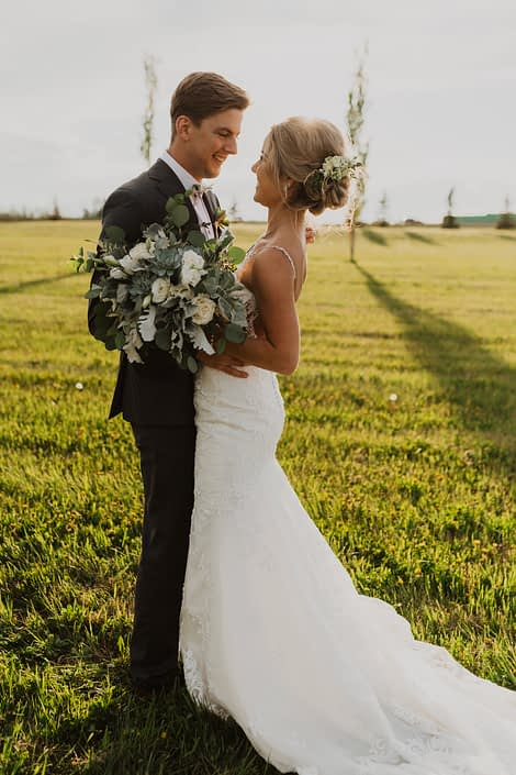 Leah and Chance's vintage white and grey green wedding; bridal bouquet featuring white playa blanca roses, lisianthus and astilbe with Blue Star succulents accented by grey toned greenery such as dusty miller and mixed varieties of eucalyptus.