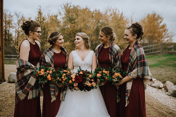 Bride and bridesmaids wearing plaid shawls for rustic fall wedding; holding bouquets designed with orange, red and yellow flowers with greenery.