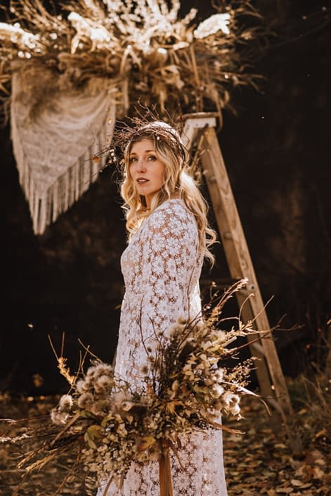fall boho bride with dried floral bouquet and boho floral fall crown in front of a pampas grass and dried floral archway piece with crochet in the woods
