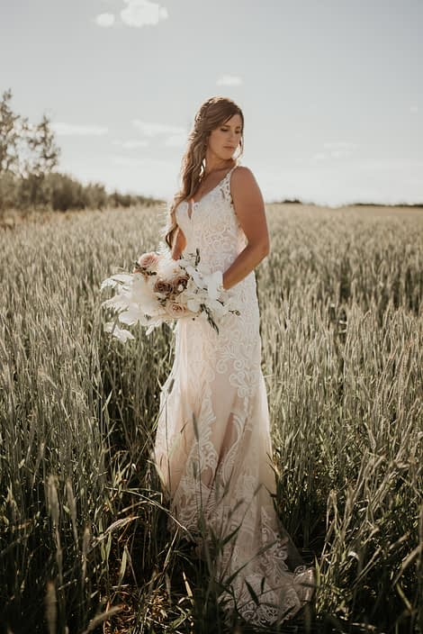Bride in a field with rustic boho bridal bouquet featuring quicksand roses, amnesia roses, ranunculus, phalenopsis orchids, astilbe, bunny tail, bleached bracken fern and olive branches