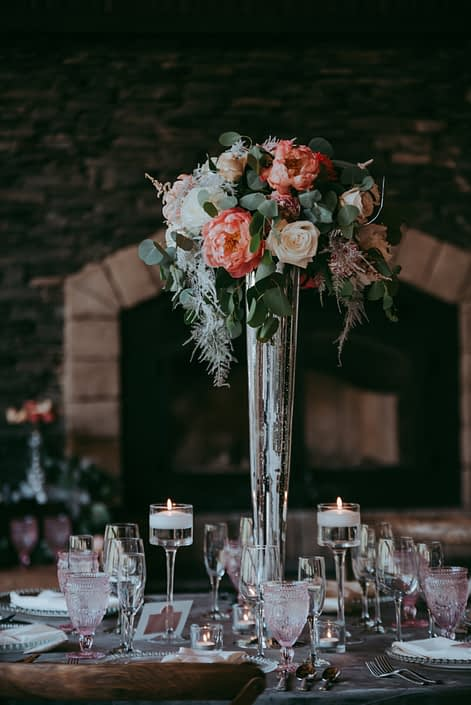 A single tall arrangement placed on a silver mercury glass vase designed with coral charm peonies, peach ranunculus, playa blanca roses, quicksand roses, light pink astilbe, silver plumosa, salal and silver dollar eucalyptus greenery.