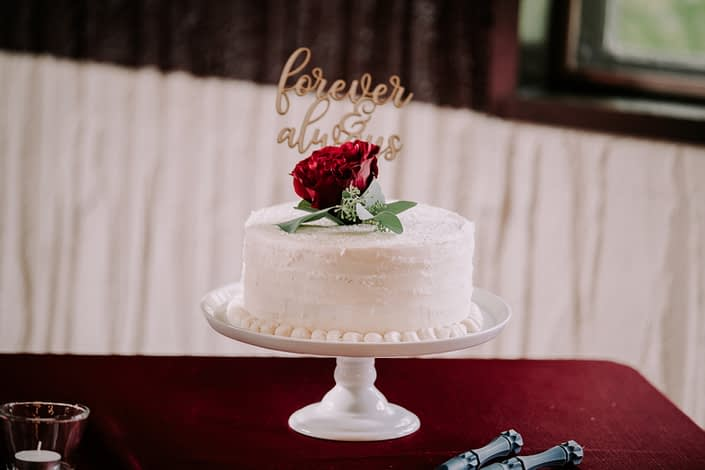 White cake topped with burgundy black baccara rose and greenery