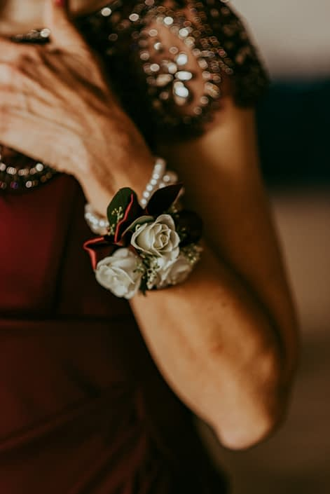 Mother of the bride's corsage designed with white spray roses accented by light pink astilbe and eucalyptus on a pearl wristlet with burgundy satin