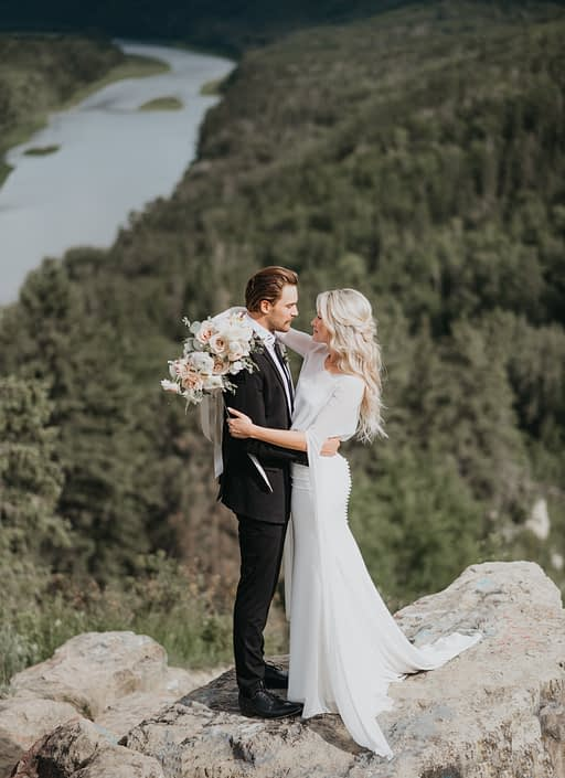 Bride and groom with pastel bouquet overlooking valley