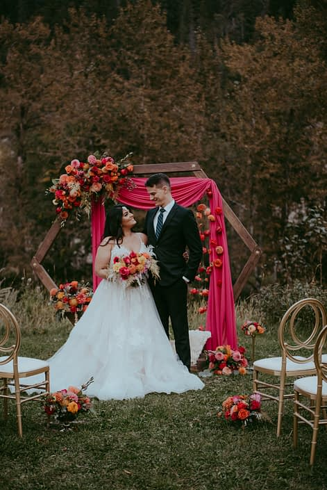 Bride and groom at the end of the aisle in front of wooden hexagon archway decorated with fuchsia and orange floral arrangements and drapery