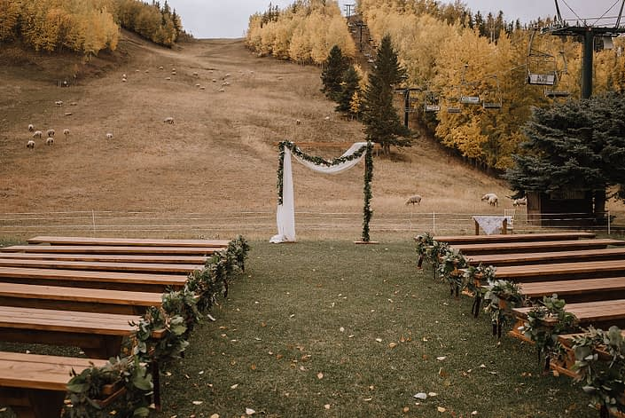 Eucalyptus rings used as ails markers n rustic benches for a ceremony at Canyon Ski Resort with a draped fabric and garland archway