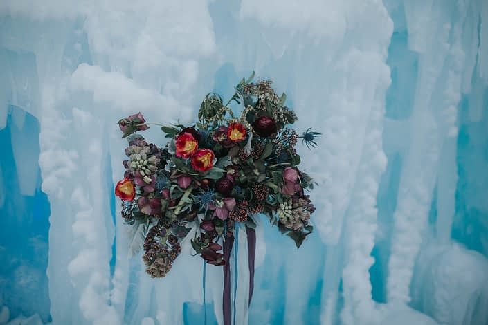A loose and natural bridal bouquet at the edmonton ice castles de signed with burgundy frittilaria, burgundy ranunculus, red tulips and burgundy helleborus